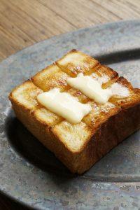 厚く切った食パンは、格子状に深めに切り込みを入れ、薄切りにした加塩の『よつ葉バター』をのせて軽くトースト