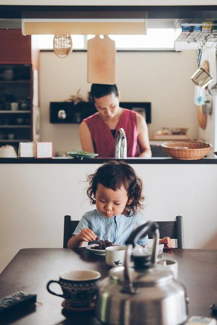 娘さんの奥で奥さんが洗い物をしている写真